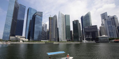 Boat manoeuvres in front of skyscrapers of Marina Bay Financial Centre in Singapore
