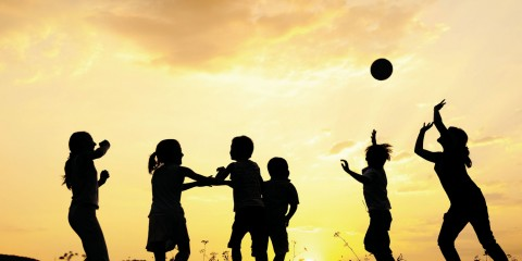 Silhouette, group of happy children playing on meadow, sunset, s