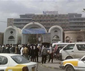 Onlookers gather outside the al-Jumhori hospital, as smoke is seen rising from a room on the top level of the building, in Sanaa