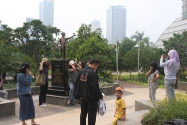 berfoto-foto di depan patung obama