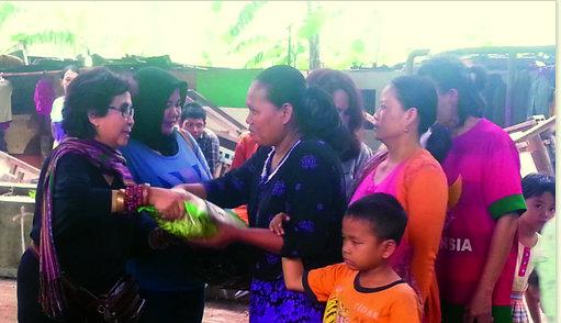 Membagikan beras kepada warga di kolong jembatan Jelambar, Petak Seng, Jakarta Barat